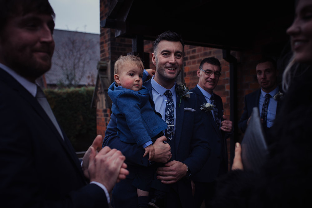 The groom and his son stand outside the church