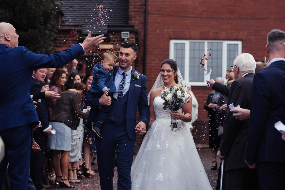 The bride and groom get covered in confetti outside church