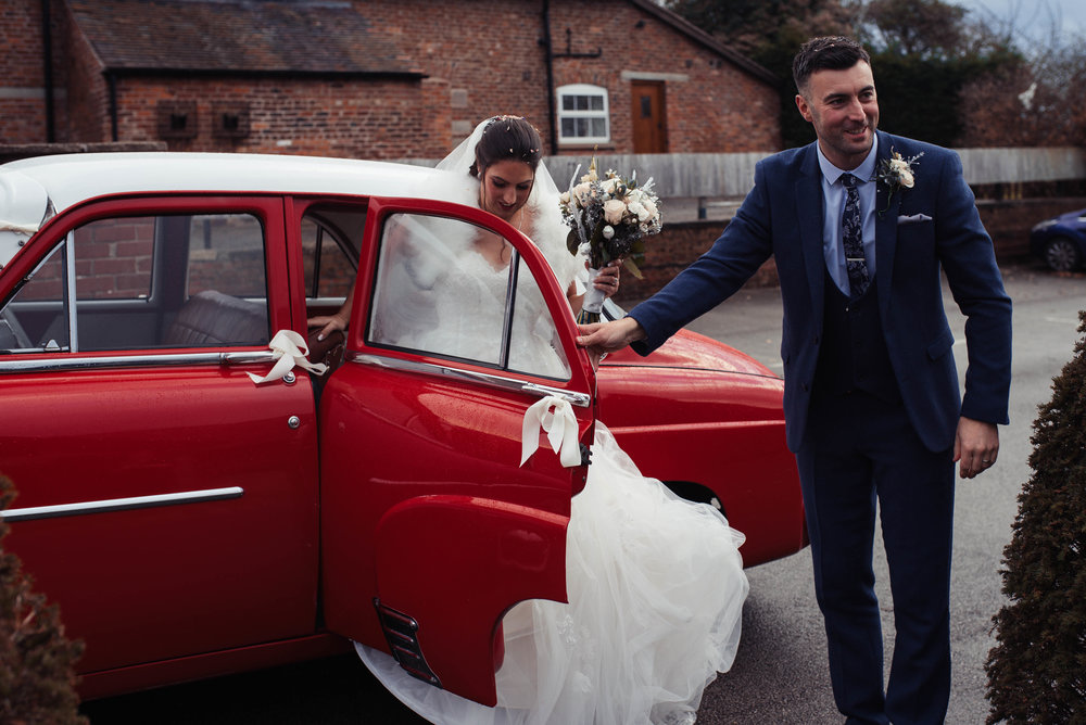 The groom opens the door of their red wedding car at sandhole oak barn