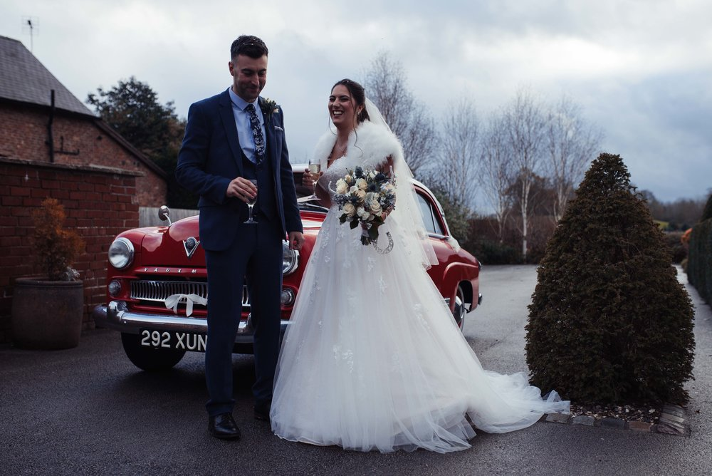 The bride and groom stand and have a giggle together in front of their wedding car