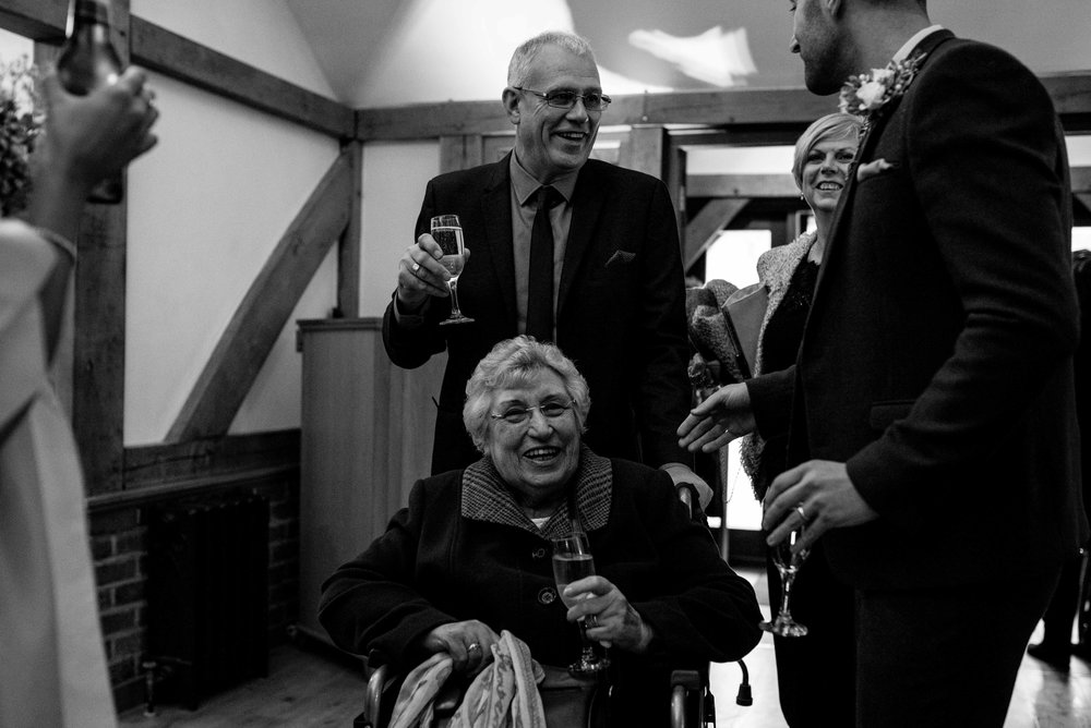 An elderly relative is wheeled into the reception at Sandhole oak barn