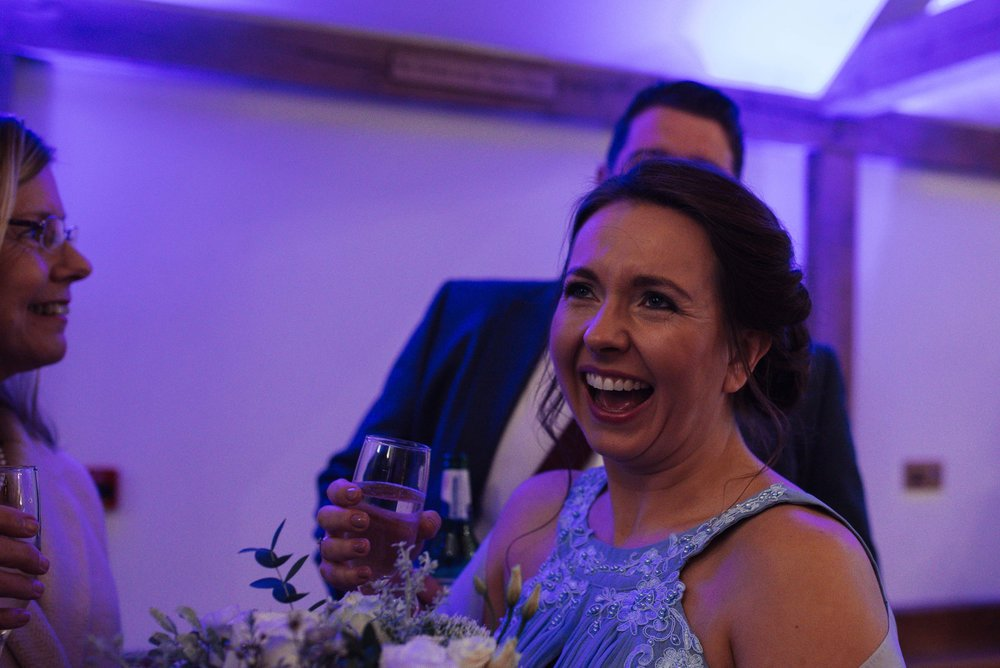 The bridesmaid laughs straight into the camera