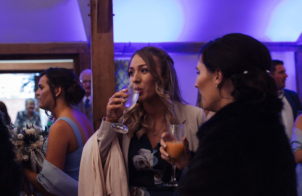 A wedding guest drinking a glass of prosecco