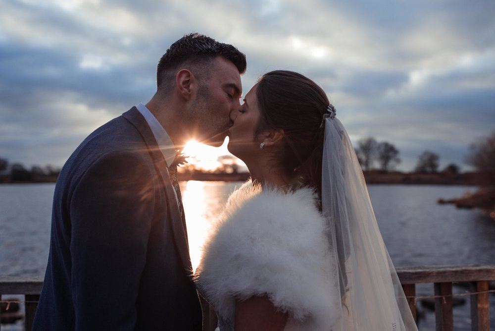 The bride and groom kiss in front of a sunset