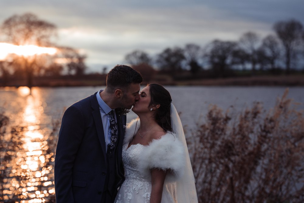 The bride and groom have a kiss with the sunset behind them