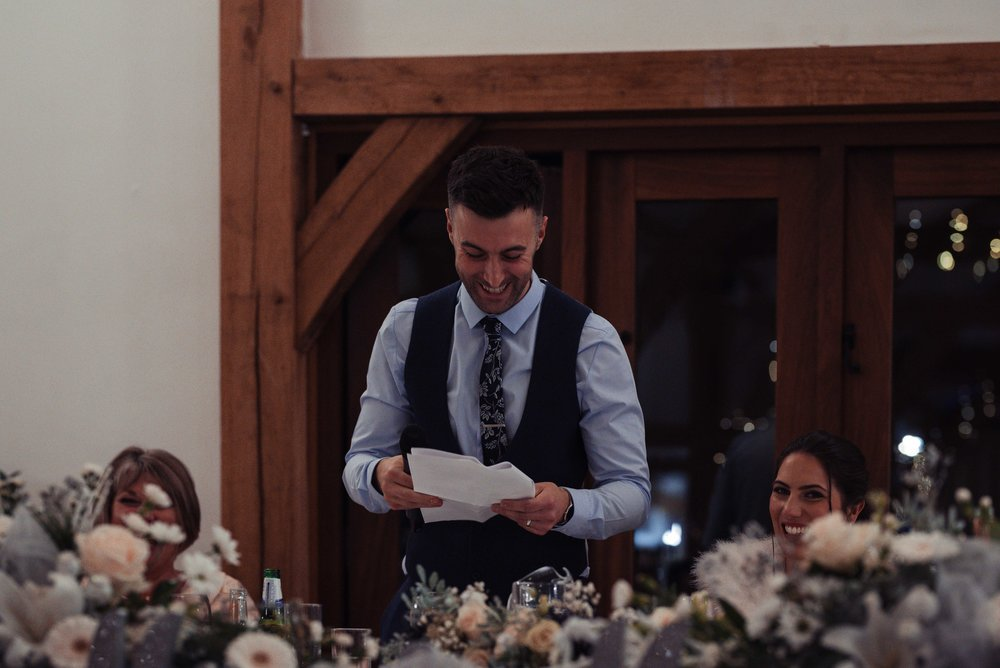 The groom delivers his speech in the barn