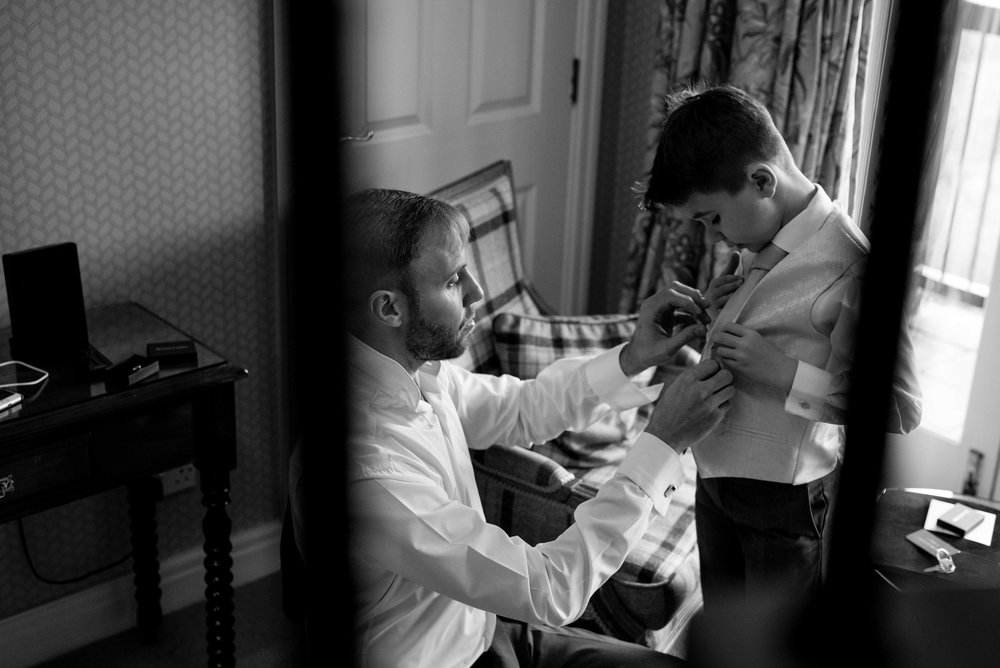 The groom helping to dress his son for the wedding ceremony