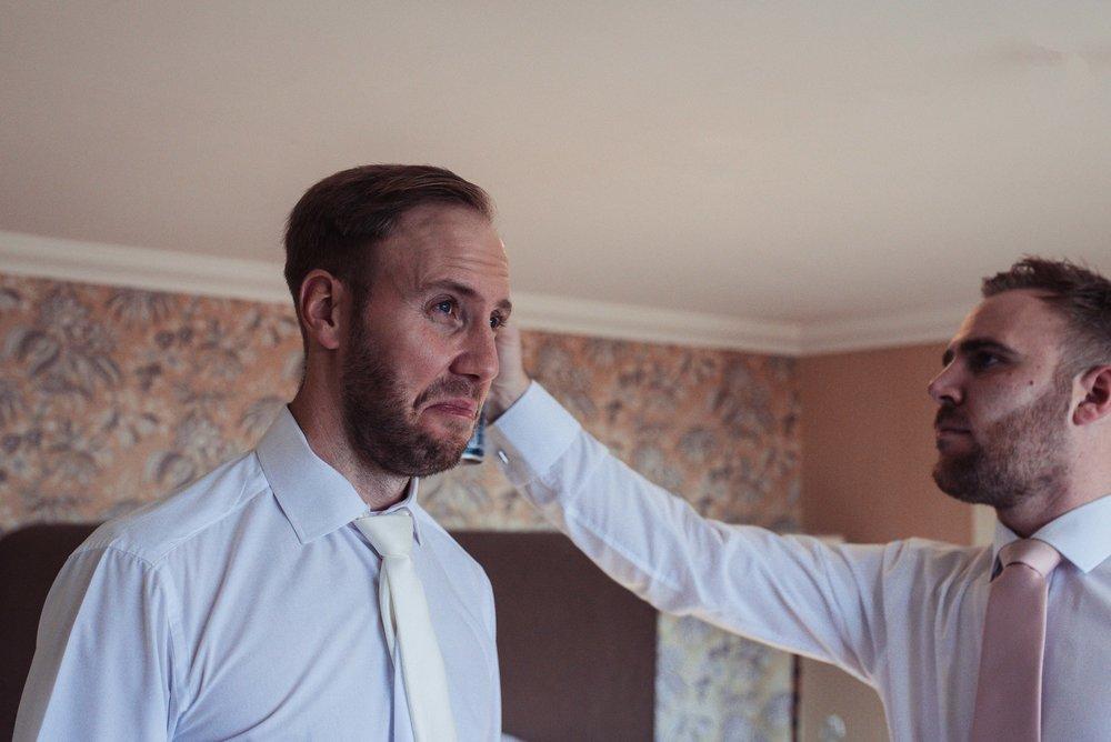 The groom pulls a funny face as the best man sprays hairspray on his hair