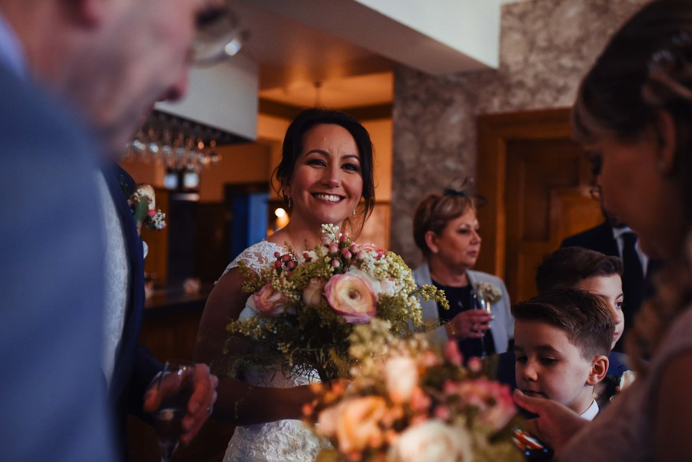 The bride shows her flowers to her wedding guests during the drinks reception