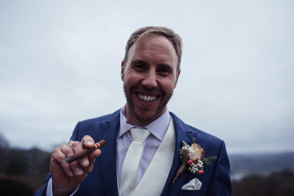 The groom with a dusky pink tie holds a cigar and looks straight into the camera