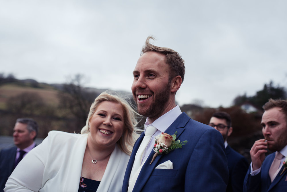 A wedding guest dressed in a white jacket snuggles up to the groom and has a giggle
