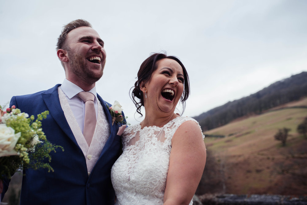 The bride and groom laughing out loud when posing for a guests photo