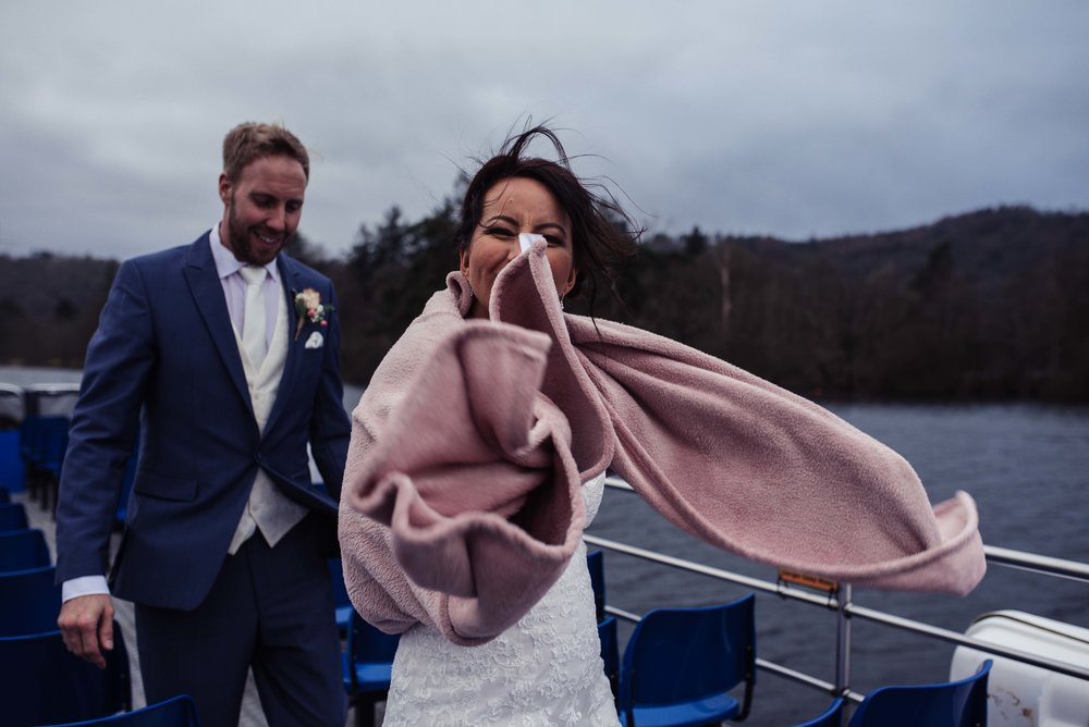 A very windswept bride and groom with the bride wrapped in a dusky pink blanket