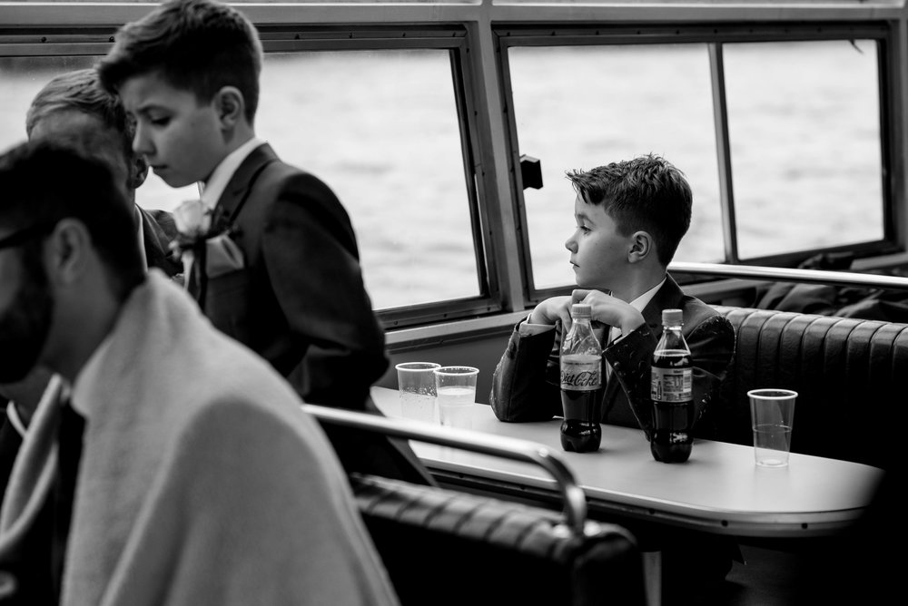 One of the bride and grooms children sits and looks out of the window on the boat trip
