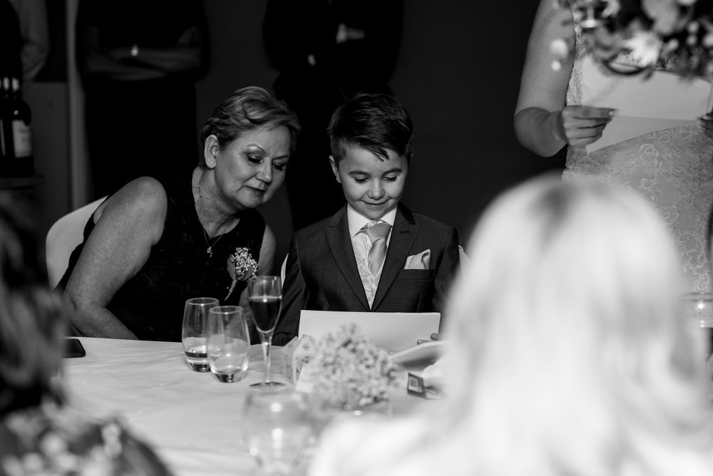 The brides mum and their son look at a photo during the speeches