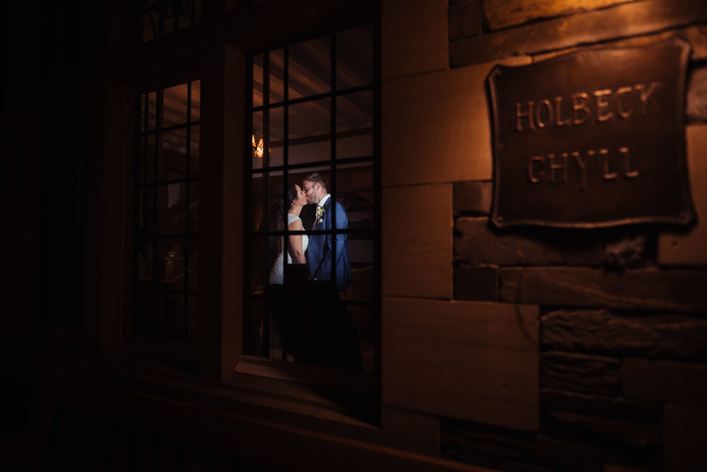 Flash-lit wedding couple shot from outside the building looking through the window