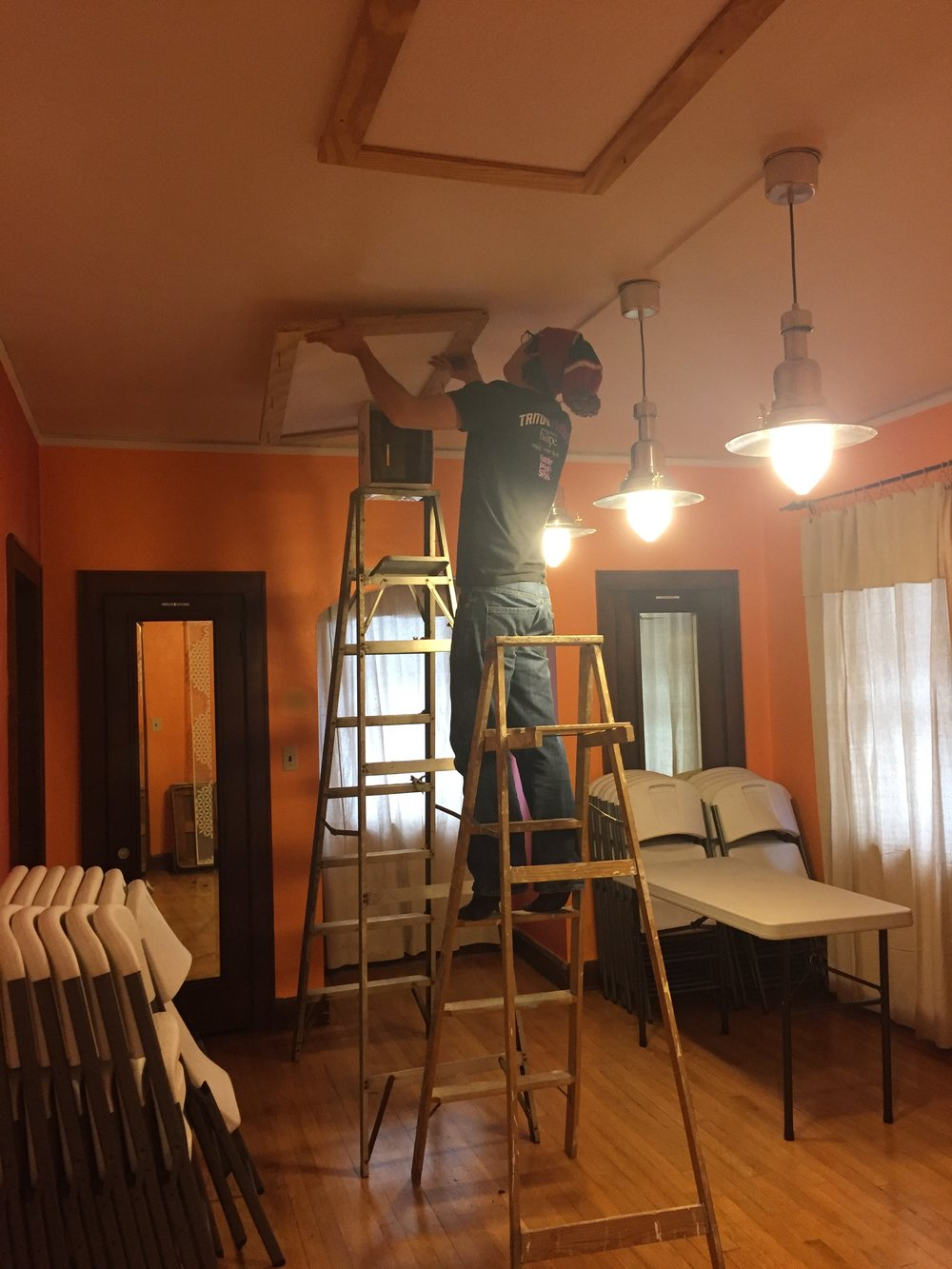 Andrew installing sound-dampening panels in the dining room.
