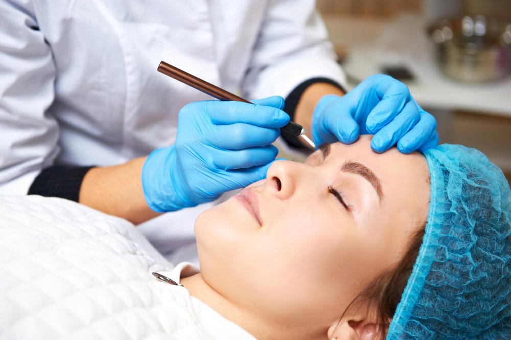 Permanent make-up wizard makes eyebrow correction procedure.jpg