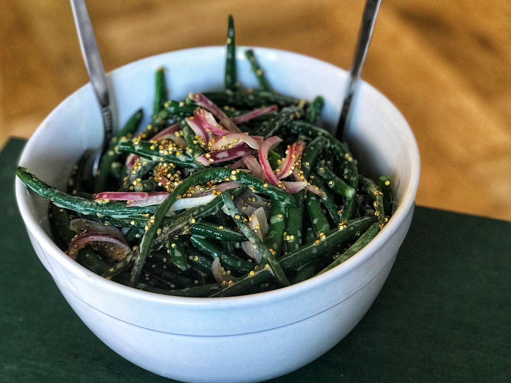 Green bean salad with crispy quinoa, pickled red onion, and lemon-tahini dressing