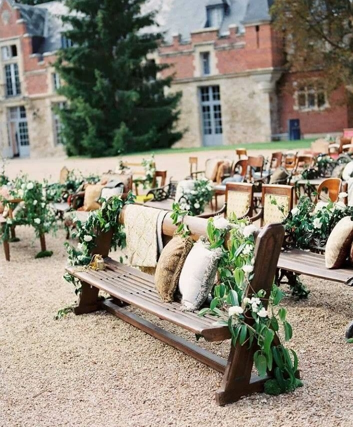 Wedding ceremony seating including a mix of pews, benches, and chairs adorned with greenery and pillows.