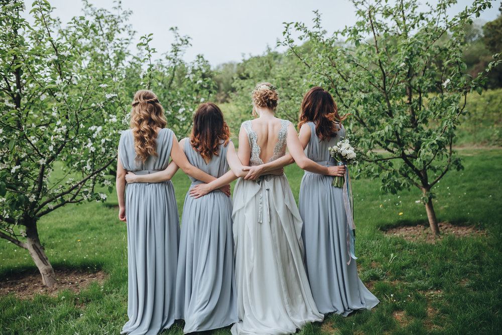 A bride hugging her bridesmaids dressed in grey-blue dresses for a garden wedding.