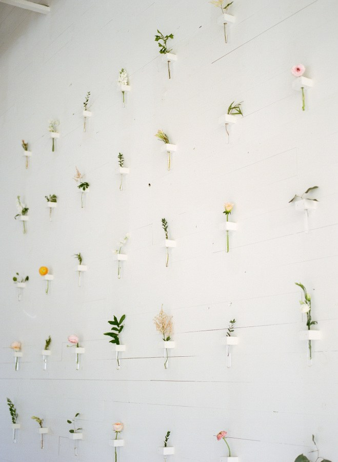 A modern floral wall with botanical bud vases for a minimalist wedding.