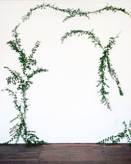 This minimalist ceremony backdrop with only greenery directs guest's all of the guests' attention on the bride and groom.