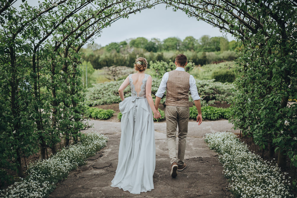 A bohemian bride and groom hold hands to sneak away for a private moment under a tunnel at their outdoor wedding venue.