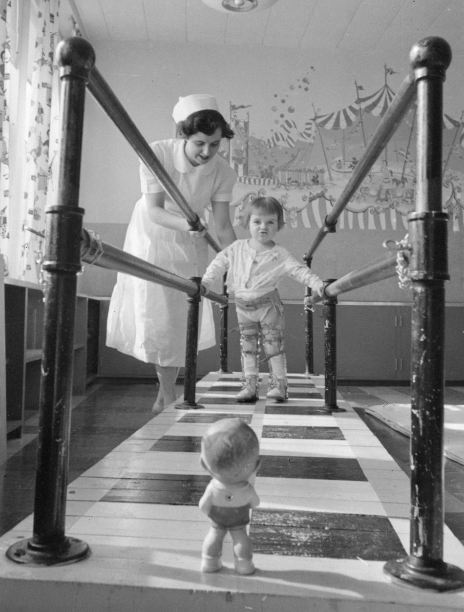 """Mrs. E. Marr, physiotherapist, with Dorothy Gifford, 2½, at the walking bars in the polio clinic, Sudbury General Hospital, Sudbury, Ont.,"" March 1953. Photograph, Chris Lund."