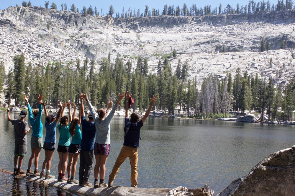 trail group stands on log, celebrate beauty of yosemite national park.