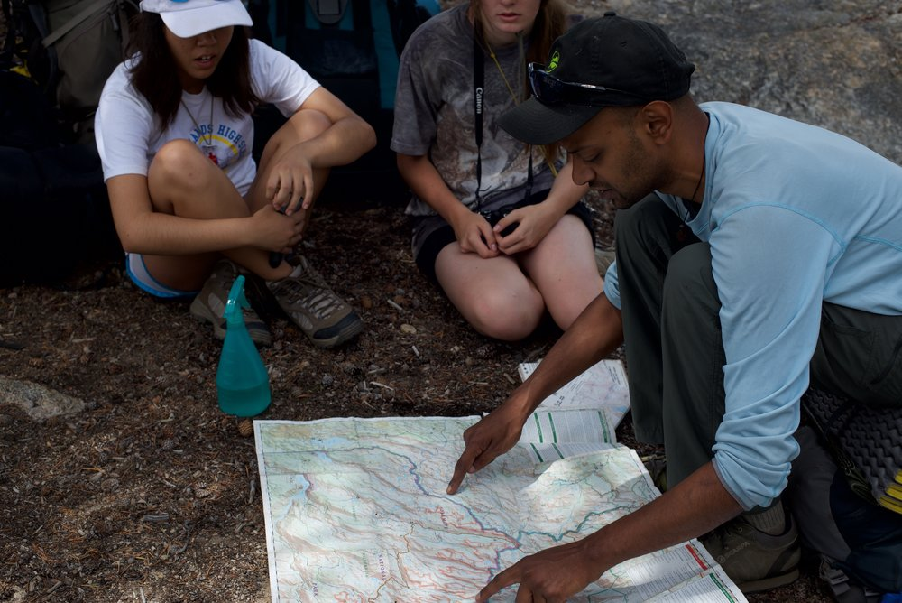 Environmental Teacher Shows Students Map in woods in Yosemite National Park, CA