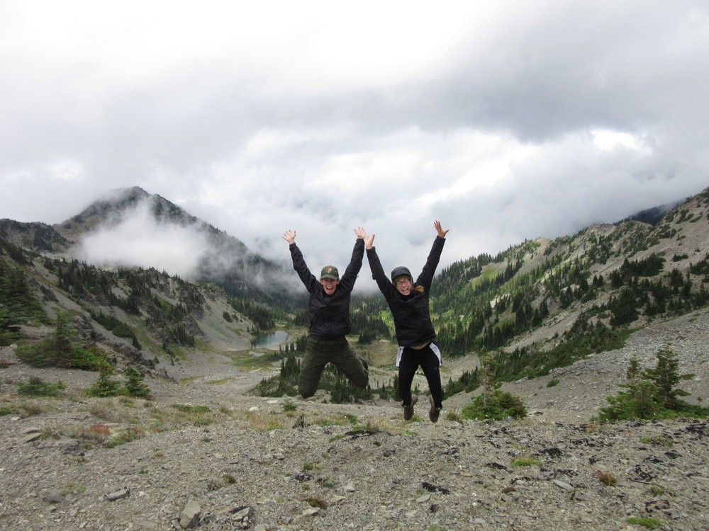 Two educators celebrate reaching mountain pass in Olympic National Park, Washington State