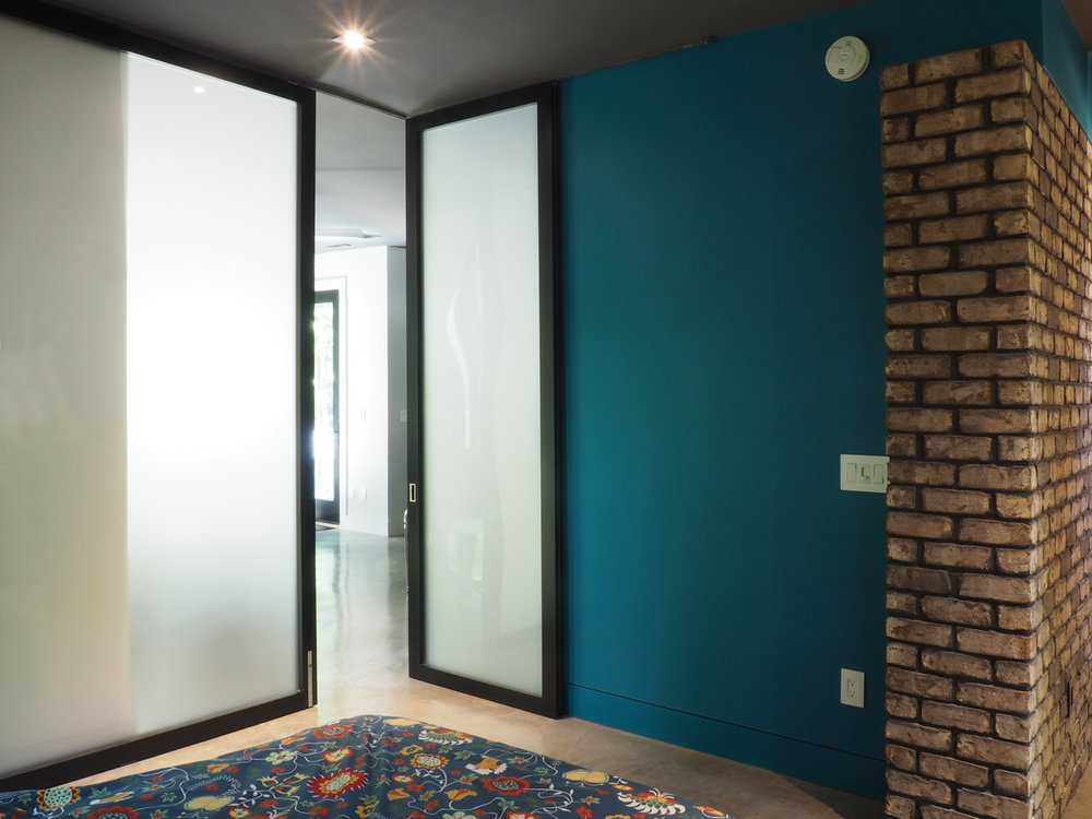 Two large contemporary frosted glass sliding panels provide for privacy in the master bedroom area downstairs, while offering space and views to the living area during the day.