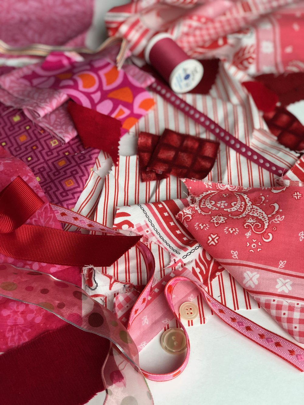 Assorted red and pink fabrics and ribbons