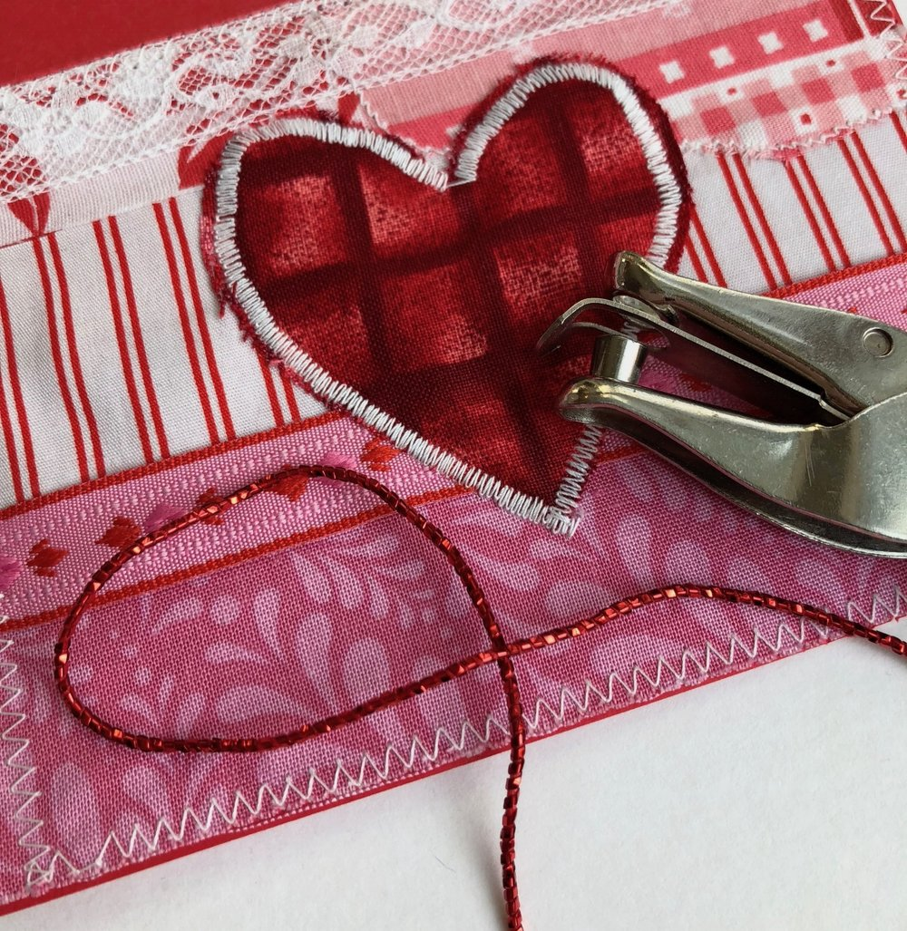 4 - After completing your stitching, punch two holes about an inch apart somewhere on your card. Tie a piece of cording or ribbon on the card. Now just embellish with any other buttons or small objects as desired!