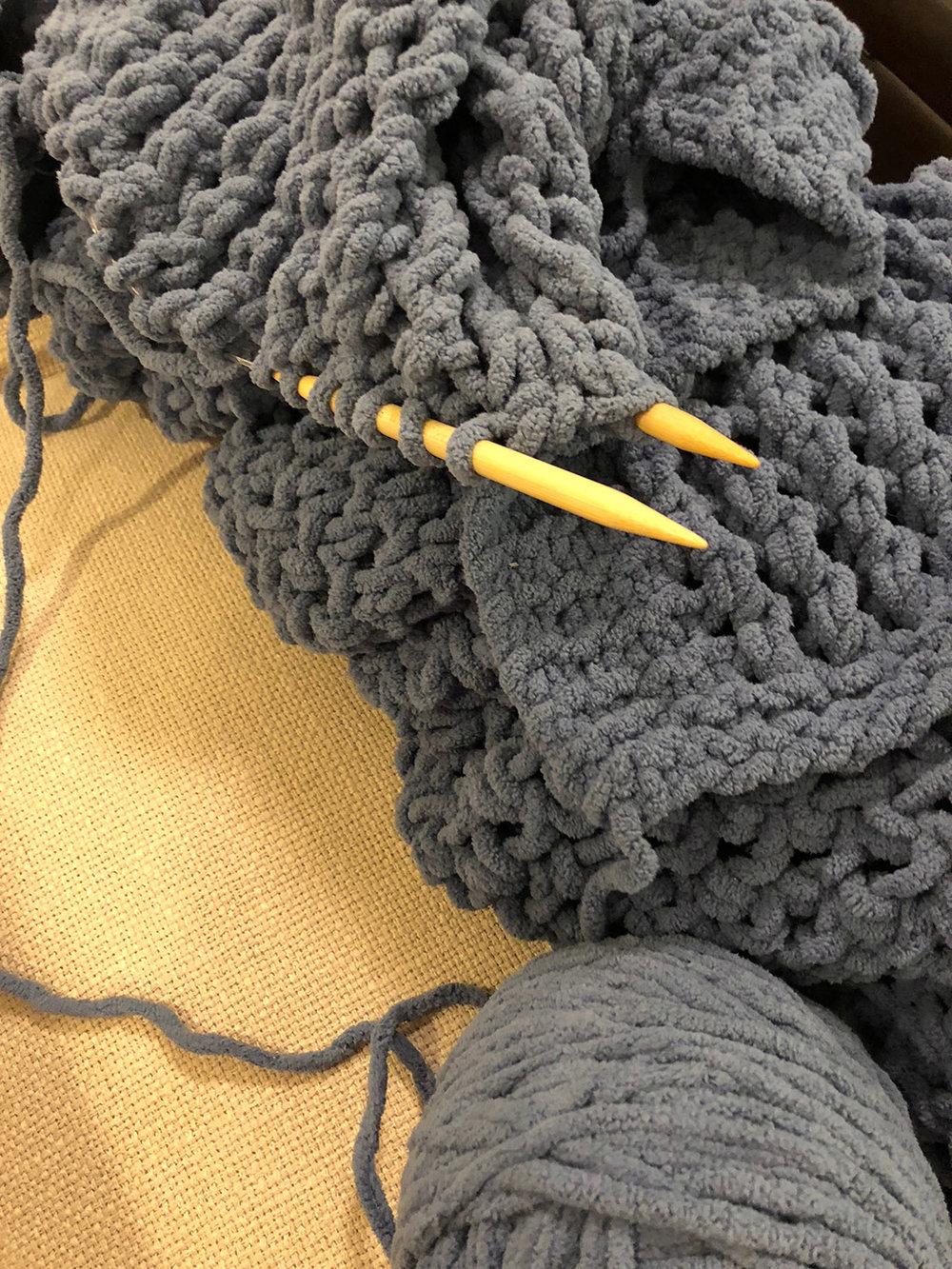 Hand knitting needles with chunky yarn throw