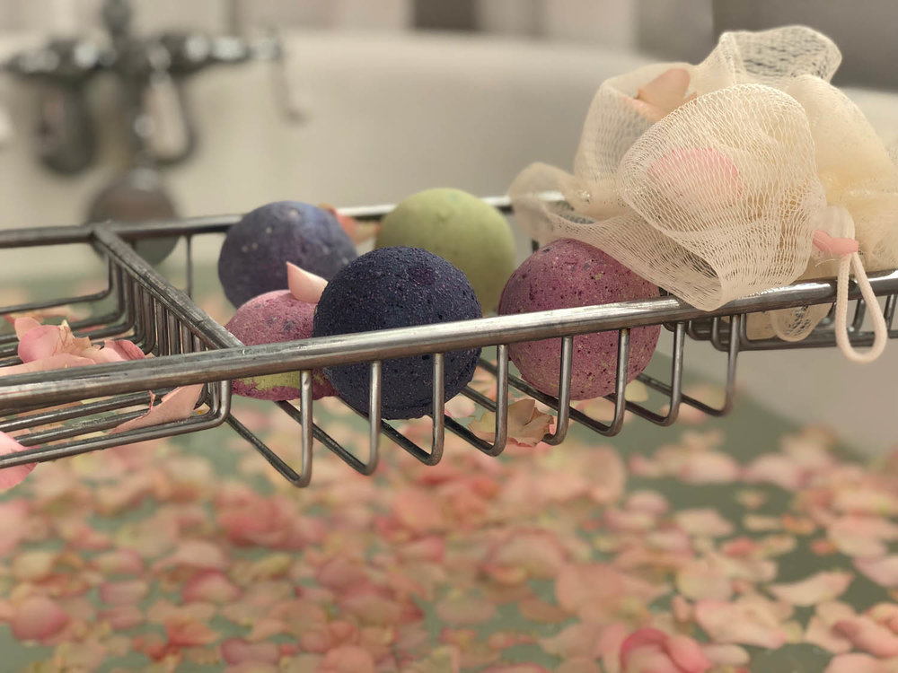 Hand made bath bombs on rack in antique claw-foot tub