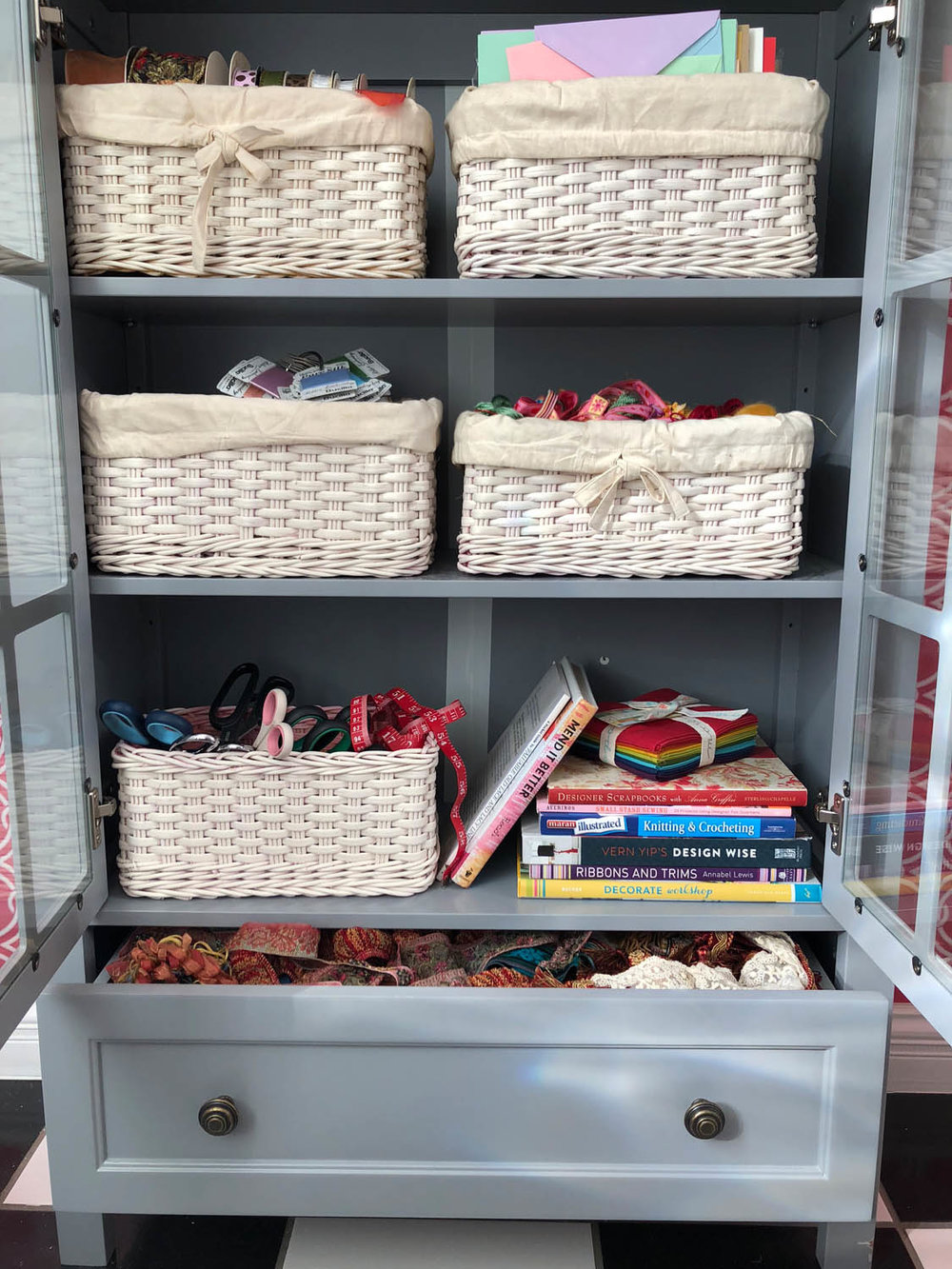 Painted craft storage baskets in glass-doored bookshelf