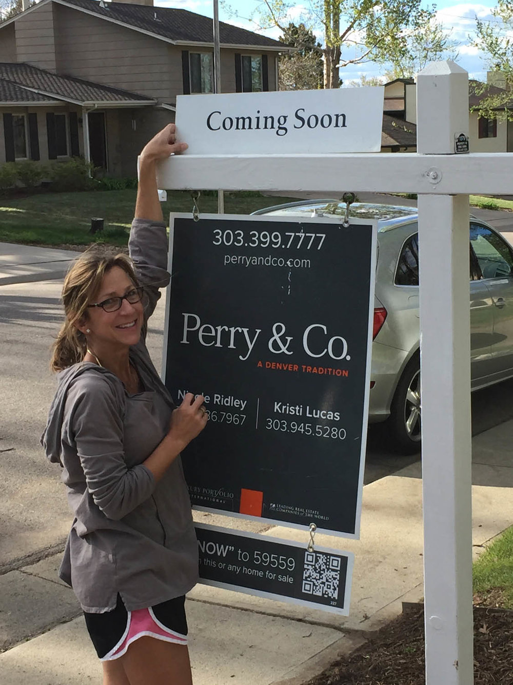 Ashley putting up the for sale sign at Long Street house flip