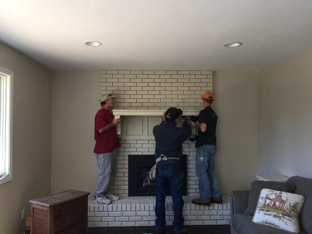 contractors hanging fireplace mantel
