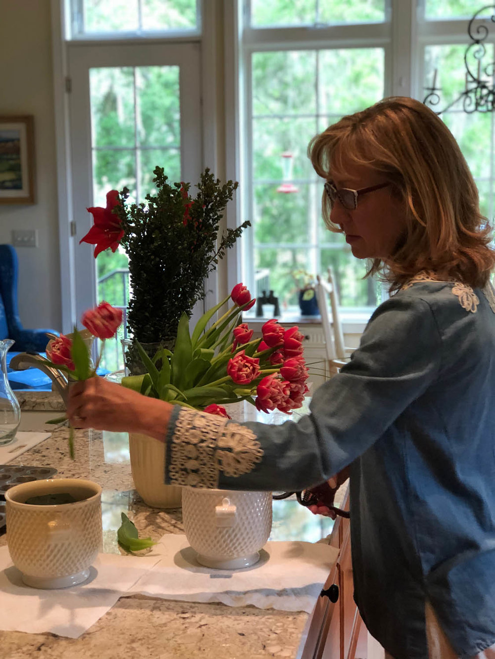Ashley arranging flowers in the kitchen