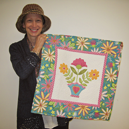 Ashley holding the quilt made for her by Erin Russek