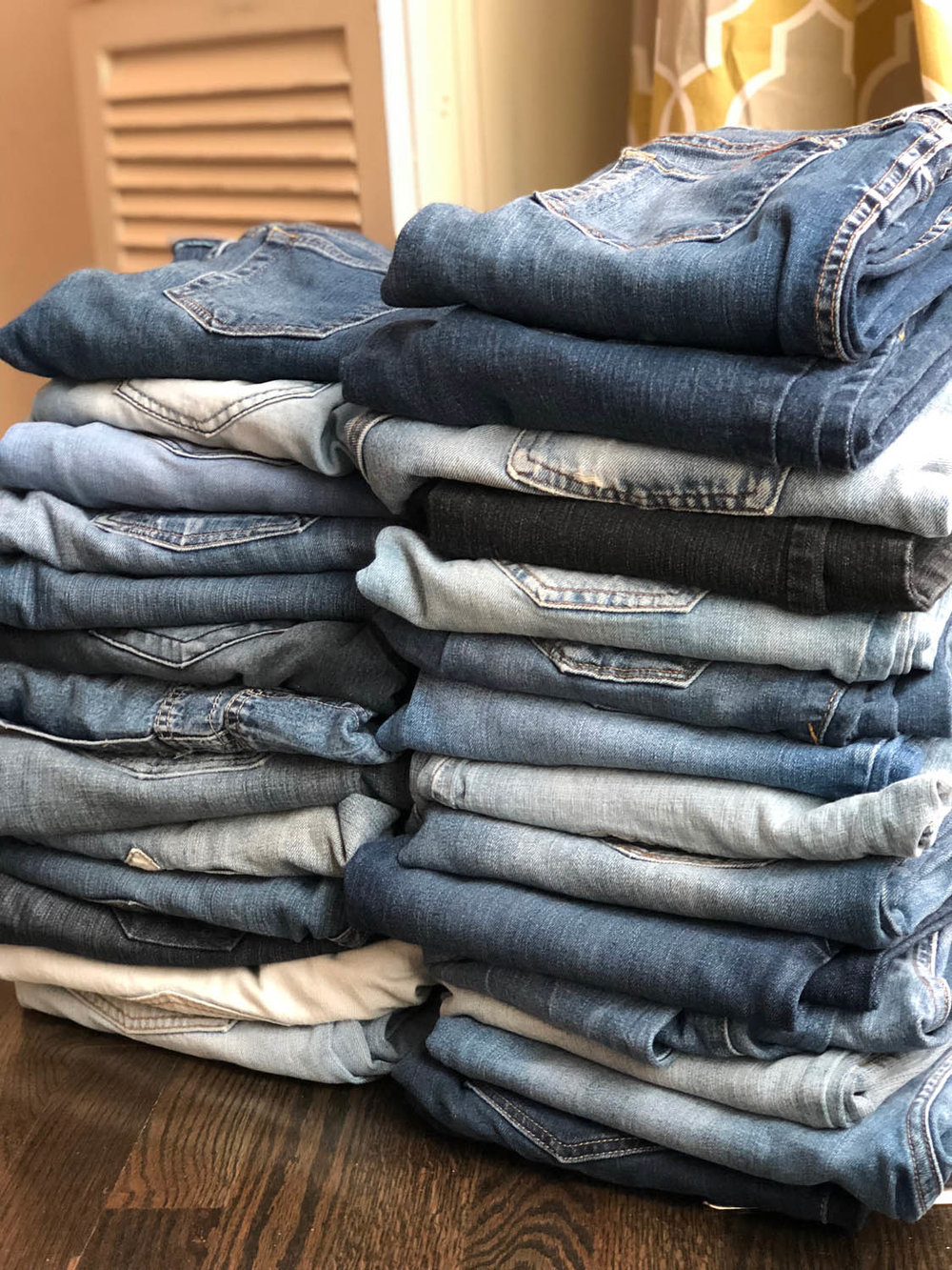 pile of folded denim blue jeans