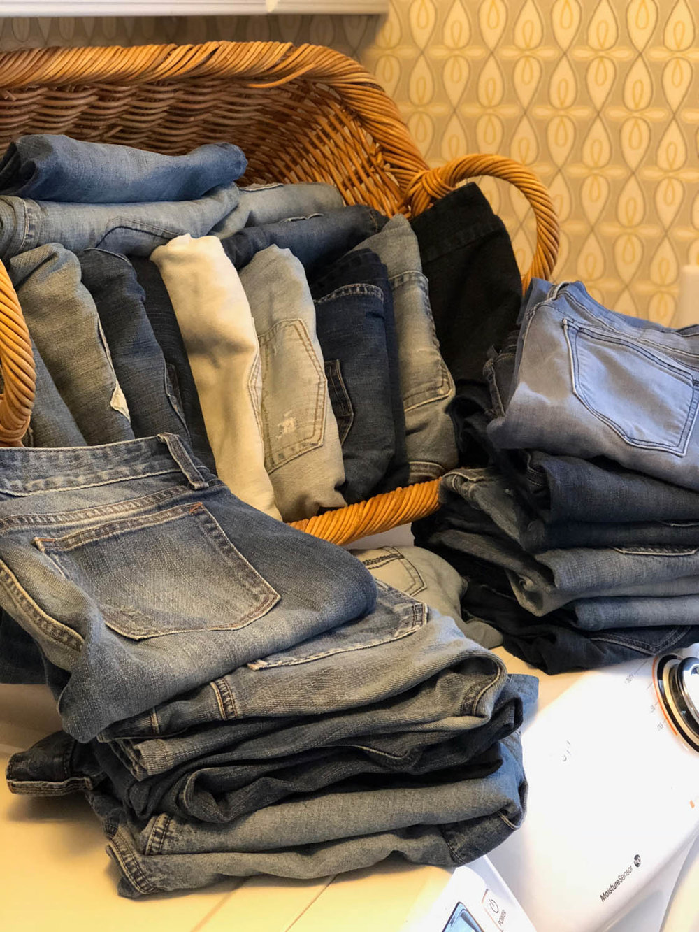 folded denim blue jeans in laundry basket