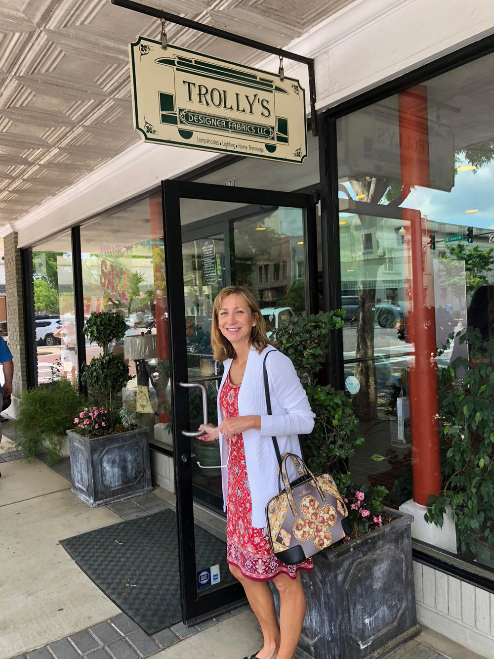 Ashley at the store entrance of Trolly's Designer Fabrics, LLC