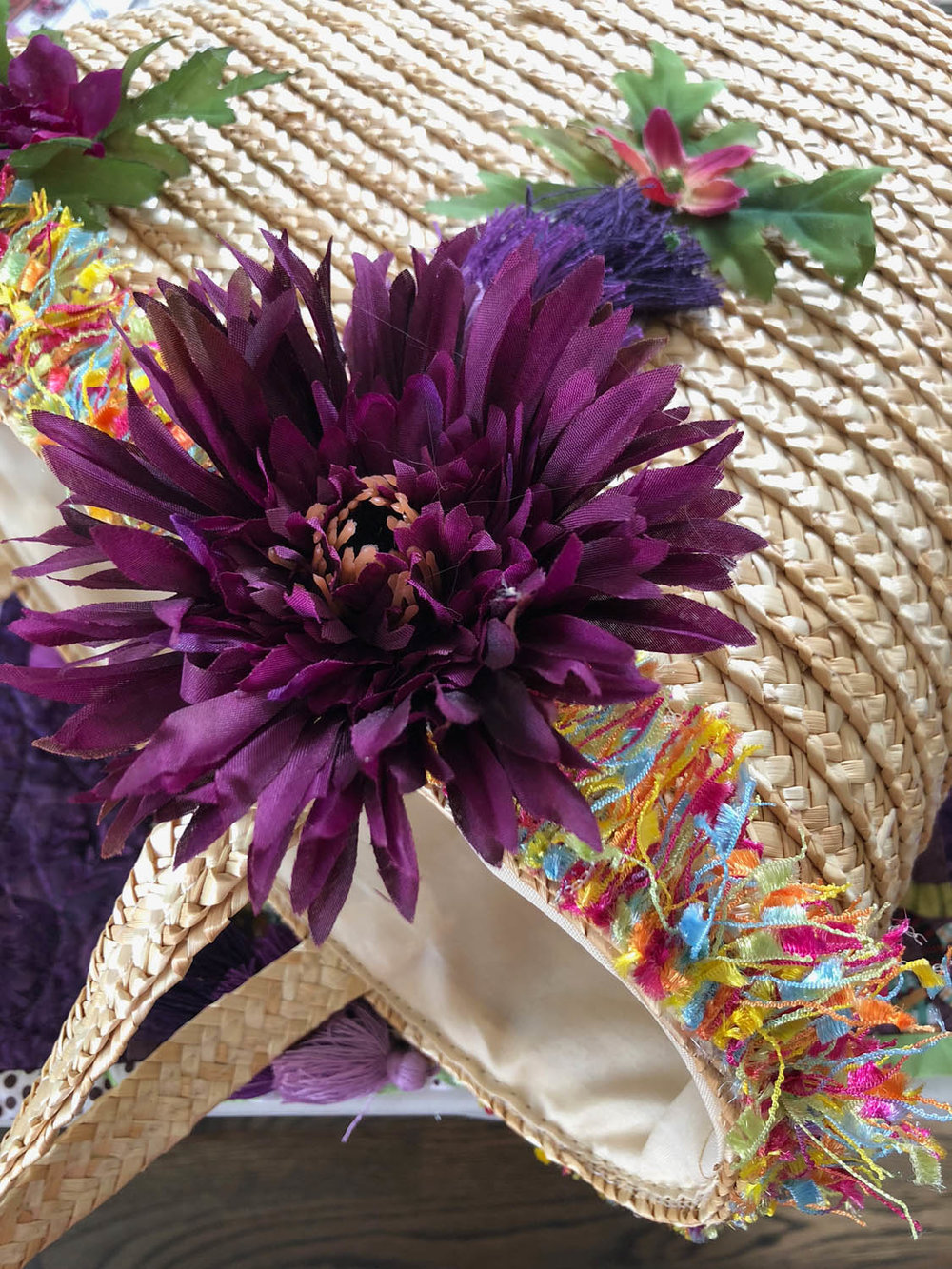 large silk flower on an embellished straw tote