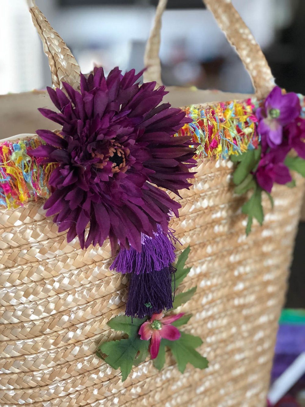 flowers and trim on an embellished straw tote