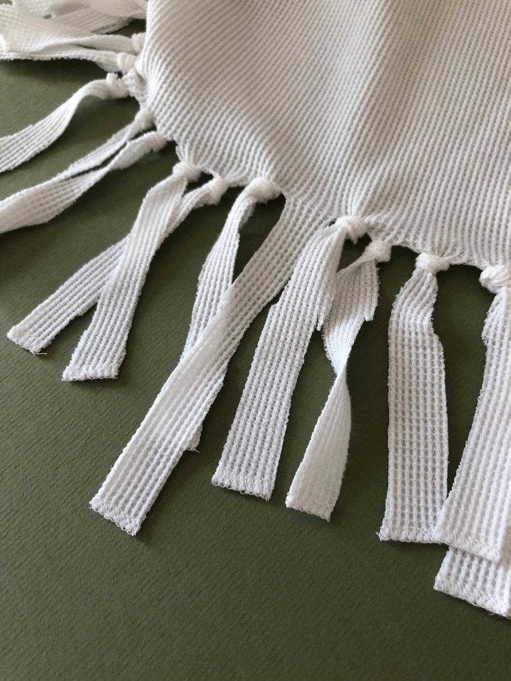 close up of fringe on long sleeve t-shirt