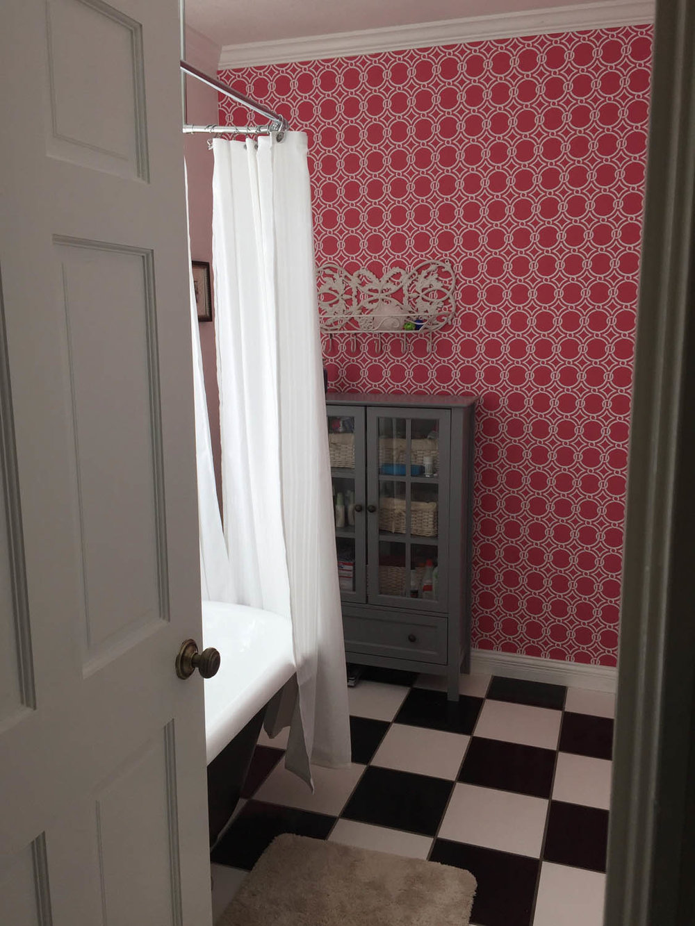 Remodeled master bathroom with clawfoot tub and pink wallpaper at Curtice Cottage.