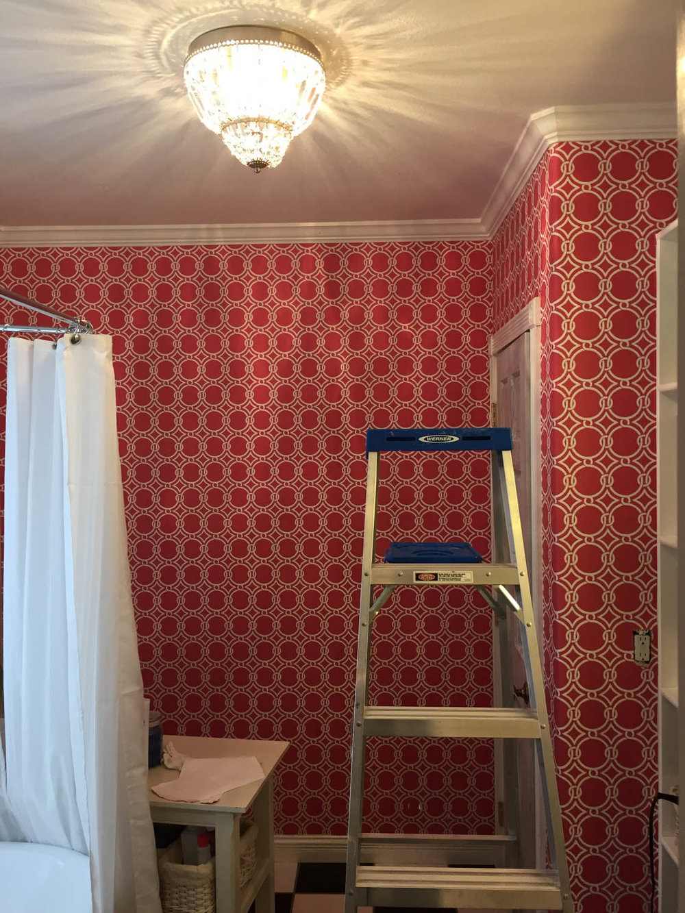 Finished pink wallpaper in master bathroom with new light fixture